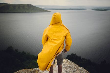 Hipster traveler in yellow raincoat standing on cliff and looking at lake in windy moody day. Wanderlust and travel concept. Man hiking in Norway on foggy day. Atmospheric moment 스톡 콘텐츠