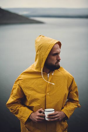 Brutal bearded man in yellow raincoat holding metal mug and traveling on cliff in rainy windy day with view on lake. Atmospheric moment. Wanderlust. Hipster man hiking in Norway