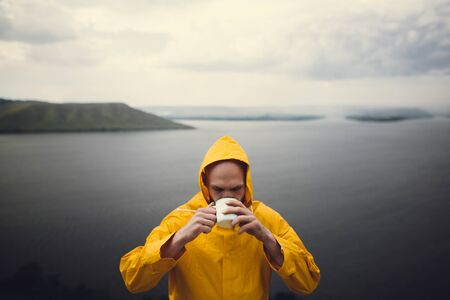 Hipster traveler in yellow raincoat holding metal mug and standing on cliff in rainy windy day with view on lake. Wanderlust and travel. Brutal bearded man hiking. Atmospheric moment