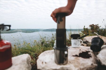 Focus on grass on cliff and blurred image of traveler pressing aeropress on metal mug on cliff at lake, brewing alternative coffee at camping. Making hot drink at picnic outdoors