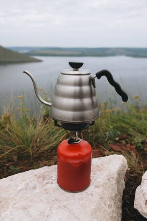 Brewing coffee in the morning while camping on cliff on background of lake. Steel kettle boiling on gas primus, making hot drink at picnic outdoors. Trekking and hiking in mountains