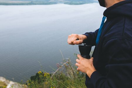 Traveler grinding fresh coffee beans while standing on cliff and looking at lake, brewing alternative coffee at camping. Making hot drink at picnic outdoors. Trekking and hiking