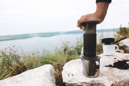 Traveler pressing aeropress on metal mug on cliff at lake, brewing alternative coffee at camping. Making hot drink at picnic outdoors. Trekking and hiking in mountains
