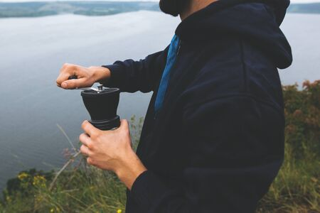 Man grinding fresh coffee beans in black grinder on cliff at lake, brewing alternative coffee at camping. Making hot drink at picnic outdoors. Trekking and hiking in mountains