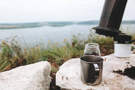 Coffee drops from aeropress on metal mug on cliff at lake, brewing alternative coffee at camping. Making hot drink at picnic outdoors. Trekking and hiking in mountains