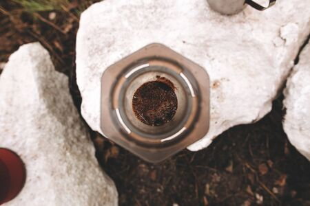Top view of brewing coffee in aeropress rock cliff at lake, brewing alternative coffee at camping. Making hot drink at picnic outdoors. Trekking and hiking in mountains