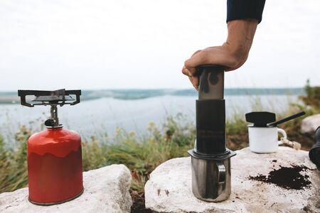 Traveler pressing hot water through coffee in aeropress on cliff at lake, brewing alternative coffee at camping. Making hot drink at picnic outdoors. Trekking and hiking in mountains