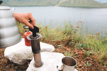 Traveler stirring hot water and coffee in aeropress on cliff at lake, brewing alternative coffee at camping. Making hot drink at picnic outdoors. Trekking and hiking in mountains Stockfoto
