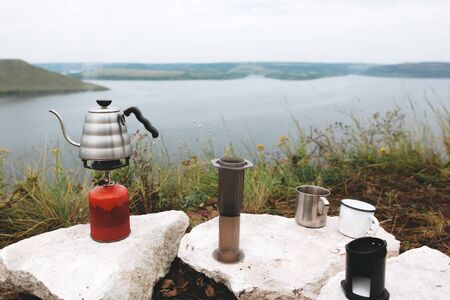 Steel kettle boiling on gas primus, metal mugs and aeropress on cliff on background of lake, brewing coffee at camping. Making hot drink at picnic outdoors. Trekking and hiking in mountains