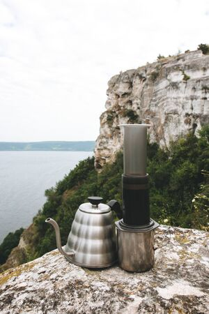 Steel kettle and aeropress on metal mug on cliff at lake, brewing alternative coffee at camping. Making hot drink at picnic outdoors. Trekking and hiking in mountains Stockfoto