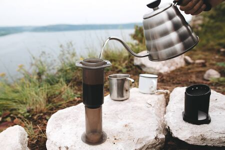 Traveler pouring hot water from steel kettle in aeropress on cliff at lake, brewing alternative coffee at camping. Making hot drink at picnic outdoors. Trekking and hiking in mountains