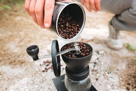 Filling grinder with fresh coffee beans on cliff at lake, preparing for brewing alternative coffee at camping. Making hot drink at picnic outdoors. Trekking and hiking in mountains
