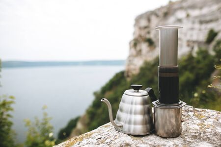 Brewing alternative coffee at camping. Steel kettle and aeropress on metal mug on cliff at lake, making hot drink at picnic outdoors. Trekking and hiking in mountains Stockfoto