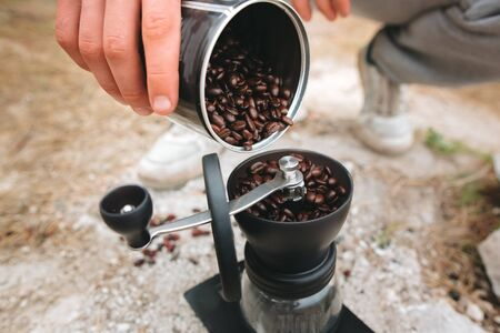 Traveler filling grinder with fresh coffee beans on cliff at lake, preparing for brewing alternative coffee at camping. Making hot drink at picnic outdoors. Trekking and hiking in mountains Stockfoto