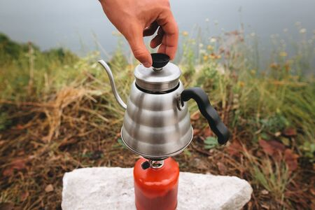 Steel kettle boiling on gas primus, making hot drink at picnic outdoors. Brewing coffee in the morning while camping on cliff on background of lake. Trekking and hiking in mountains