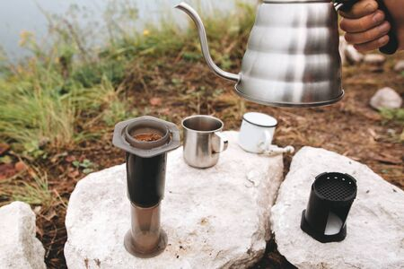 Brewing alternative coffee at camping. Traveler pouring hot water from steel kettle in aeropress on cliff at lake. Making hot drink at picnic outdoors. Trekking and hiking in mountains