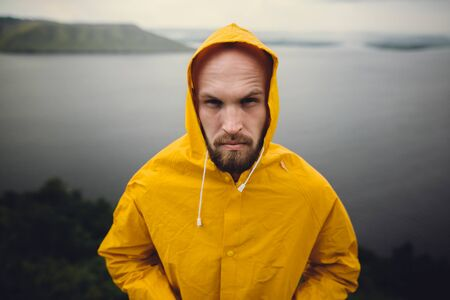 Portrait of fisherman, brutal bearded man in yellow raincoat standing on cliff in rainy windy day with view on lake. Atmospheric moment. Wanderlust, hipster man hiking in Norway