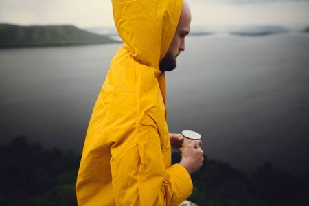 Wanderlust. Traveler in yellow raincoat holding metal mug and standing on cliff  in rainy windy day with view on lake. Hipster man hiking in Norway. Atmospheric moment