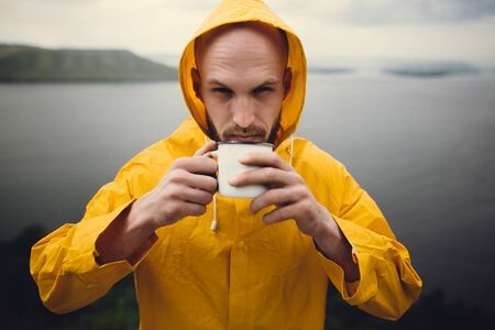 Wanderlust. Hipster traveler in yellow raincoat holding metal mug and standing on cliff  in rainy windy day with view on lake. Hipster man hiking in Norway. Atmospheric moment 스톡 콘텐츠