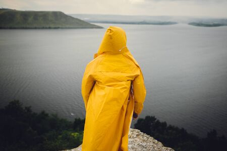 Man in yellow raincoat traveling on cliff and looking at lake in rainy windy day. Atmospheric moment. Wanderlust and travel concept. Hipster man hiking in Norway on foggy day 스톡 콘텐츠