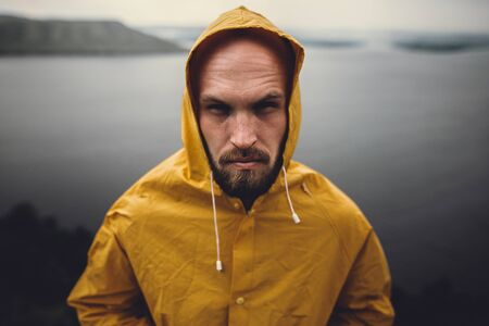 Brutal bearded man in yellow raincoat standing on cliff in rainy windy day with view on lake. Atmospheric moment. Wanderlust. Portrait of fisherman, hipster man hiking in Norway