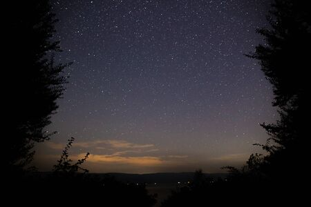 Amazing starry night sky with Milky way and falling stars above lake and trees in mountains. Beautiful night sky. Breathtaking landscape. View on sky from camp tent in woods