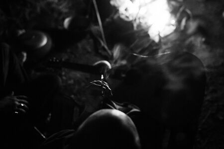 Hipster man smoking cigarette and holding acoustic guitar at big bonfire, chilling at camp in the evening. Close up on cigarette. Musician relaxing at fire. Creative photo, atmospheric moment