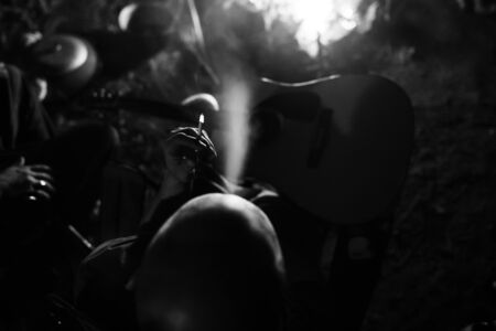 Hipster man smoking cigarette and holding acoustic guitar at big bonfire, chilling at camp in the evening. Close up on smoke. Musician relaxing at fire. Creative photo, atmospheric moment Фото со стока