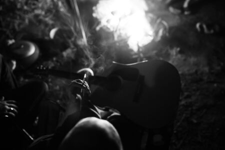 Hipster man smoking cigarette and holding acoustic guitar at big bonfire, chilling at camp in the evening. Focus on smoke. Musician relaxing at fire. Creative photo, atmospheric moment