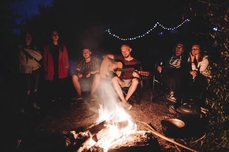 Friends travelers chilling at big bonfire, listening to acoustic music, relaxing at camp in the night forest. Group of people resting at fire in the evening, camping near lake Stock fotó