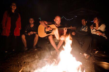 Des amis voyageurs se détendent devant un grand feu de joie, chantent des chansons et jouent de la guitare au camp dans la forêt nocturne. Groupe de personnes se reposant au feu le soir, campant dans les bois Banque d'images