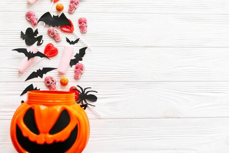 Halloween candy with skulls, black bats, ghost, spider decorations spilled from jack o lantern bucket on white wooden 免版税图像