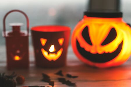 Blurred image of glowing jack o lantern face, festive candy, skulls, black bats, ghost, spider decorations on white wooden Banque d'images - 129713035