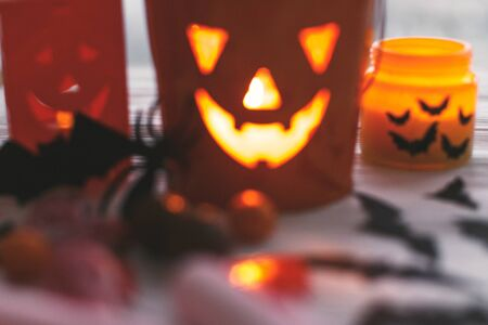 Blurred image of glowing jack o lantern face, festive candy, skulls, black bats, ghost, spider decorations on white wooden Banque d'images - 129713033