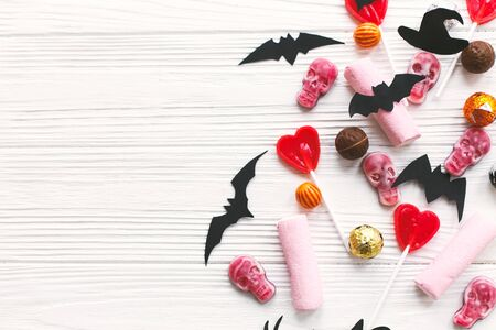 Halloween candy border with skulls, black bats, ghost, spider paper decorations on white wooden Banque d'images - 129713036