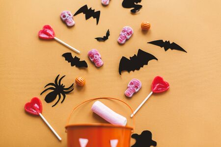 Halloween flat lay. Halloween candy skulls with black bats and ghost paper decorations on yellow Banque d'images - 129713043