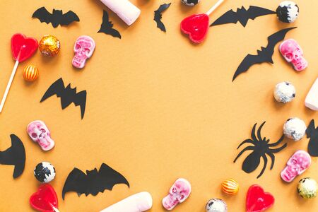 Halloween flat lay. Candy frame with skulls, black bats, ghost, spider paper decorations on yellow Banque d'images - 129713045