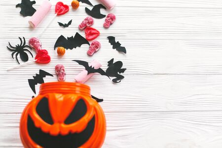 Happy Halloween. Halloween candy spilled from jack o lantern bucket with skulls, black bats, ghost, spider decorations on white wooden Banque d'images - 129713049
