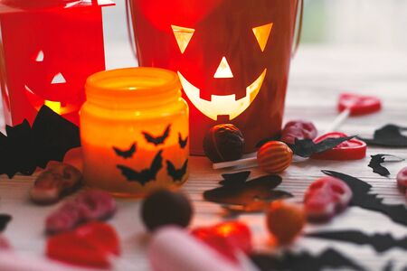 Halloween jack o lantern bucket, glowing candle, festive candy, skulls, black bats, ghost, spider decorations on white wooden Banque d'images - 129713050