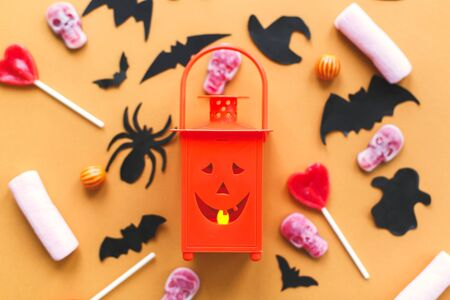 Happy Halloween. Halloween candy flat lay with jack o lantern candle on yellow paper. Banque d'images - 129713514