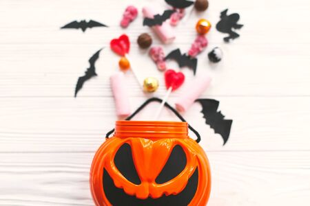 Trick or treat. Halloween candy spilled from jack o lantern bucket with skulls, black bats, ghost, spider decorations on white wooden Banque d'images - 129713516