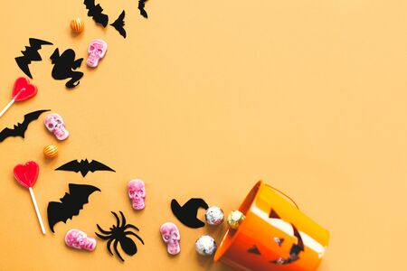 Happy Halloween flat lay, copy space. Halloween candy, skulls, black bats and ghost paper decorations scattered from evil bucket on yellow Banque d'images - 129713513