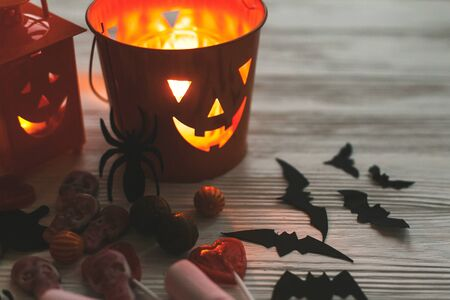 Glowing jack o lantern face, festive candy, skulls, black bats, ghost, spider decorations on white wooden Banque d'images - 129713528