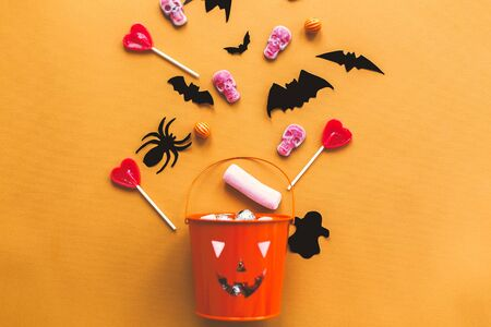 Halloween candy flat lay. Halloween candy, skulls, black bats and ghost paper decorations scattered from evil bucket on yellow Banque d'images - 129713522
