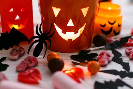 Halloween jack o lantern bucket, glowing candle, festive candy, skulls, black bats, ghost, spider decorations on white wooden Banque d'images - 129713529