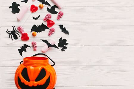 Halloween candy spilled from jack o lantern bucket with skulls, black bats, ghost, spider decorations on white wooden Banque d'images - 129713376