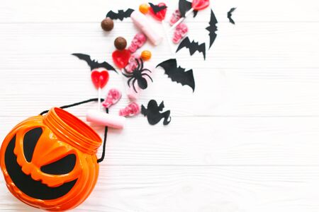 Trick or treat. Halloween candy spilled from jack o lantern bucket with skulls, black bats, ghost, spider decorations on white wooden Banque d'images - 129713380