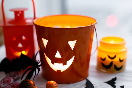 Halloween jack o lantern bucket, glowing candle, festive candy, skulls, black bats, ghost, spider decorations on white wooden Banque d'images - 129713378