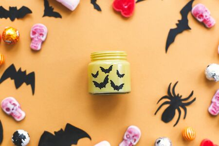 Halloween flat lay. Candy frame with candle, skulls, black bats, ghost, spider paper decorations on yellow Banque d'images - 129713382