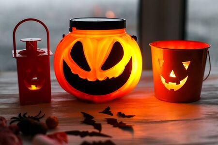 Glowing jack o lantern face, festive candy, skulls, black bats, ghost, spider decorations on white wooden Banque d'images - 129713386